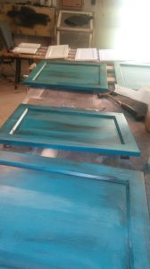 teal and turquoise with copper cabinet doors being painted