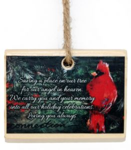 Cardinal memorial ornament with poem over evergreen background