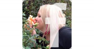 girl smelling rose with pink hair